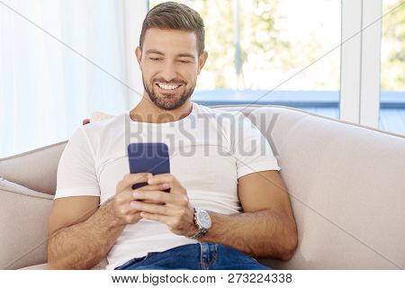 Young Man Text Messaging While Sitting On Couch At Home