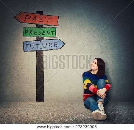 Young Woman Sitting On The Floor Looking At A Signpost With Arrows That Shows Past, Present And Futu