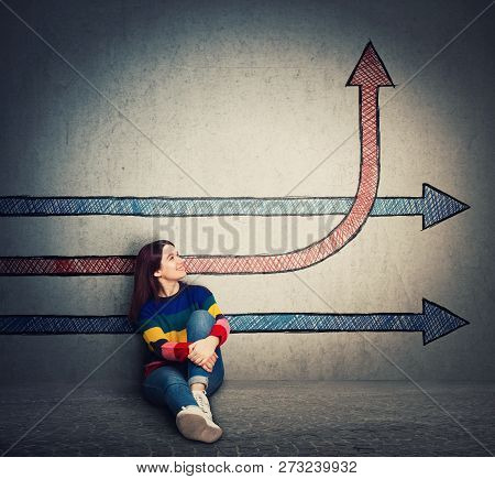 Casual Young Woman Sitting On The Floor Looking At Arrows One Changing Direction, Benting Go Up, As