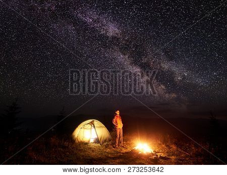 Night Camping In Mountains. Tourist Woman Standing Near Illuminated Tent And Brightly Burning Campfi