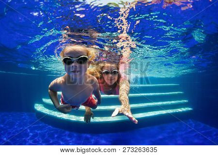 Happy Family - Mother, Baby Boy In Goggles Learn To Swim And Dive Underwater With Fun In Swimming Po
