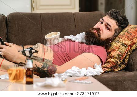 Sick Man Lying On Sofa Checking His Temperature Under A Blanket At Home In The Living Room. Dramatic