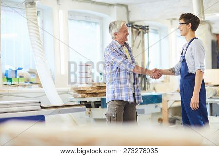 Cheerful excited mature carpenter with gray hair making handshake with young employee in overall while they standing in modern workshop