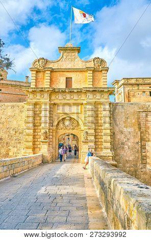 Mdina, Malta - June 14, 2018: The Walk Along The Medieval Stone Bridge To The Mdina Gates, The Main