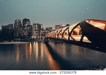 Calgary cityscape with Peace Bridge and downtown skyscrapers in Alberta at dusk, Canada.