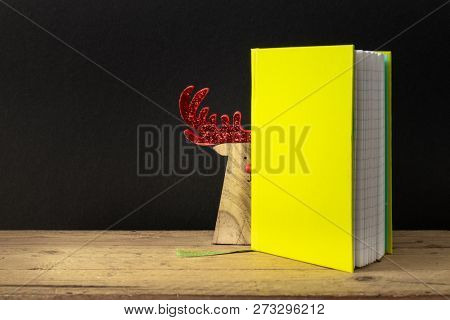 An image of a yellow green note book with hidden reindeer on a wooden table