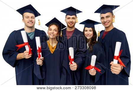 education, graduation and people concept - group of happy graduate students in mortar boards and bachelor gowns with diplomas over white background