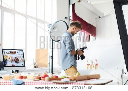 Portrait Of Smiling Male Photographer Looking At Pictures In Camera While Working In Photo Studio Sh