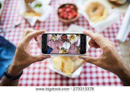 Top View Closeup Of Unrecognizable Man Holding Smartphone And Taking Pictures Of Food On Picnic Tabl