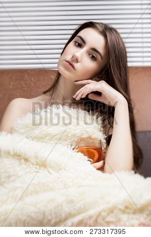Pensive Young Woman With Cup Of Tea Relax On Sofa