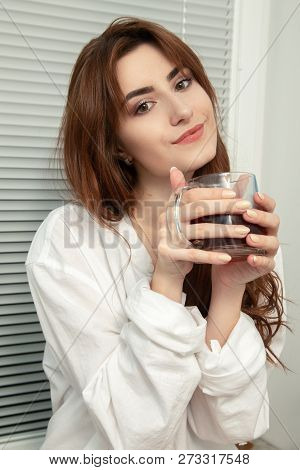Pensive Beautiful Young Woman With Cup Of Tea Looking At Camera Smiling