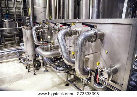 Modern Brewery Interior. Industrial Stainless Steel Pipes Connected With Vats And Control Valves.