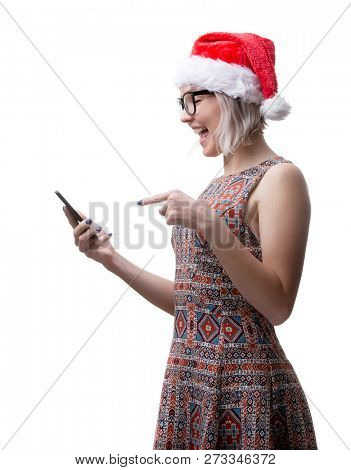 Picture of blonde in glasses and Santa's cap with phone in hand on empty space