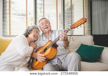 Meaningful Moments. Lover Senior Couple Sing A Song Together. Husband Playing A Guitar And Wife Is S
