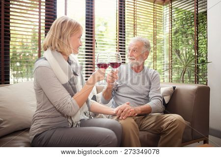 Happy Anniversary.  Retired Couple Is Hitting A Glass Of Wine Celebrating A Wedding Anniversary.