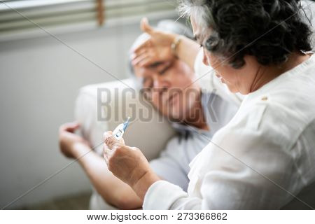 Sick Asian Senior Man Lying On Sofa While His Wife Holding And Looking To Thermometer. Illness, Dise