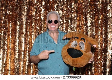 Photo Booth. A man poses and smiles with an cartoon animal head in a Photo Booth. Gold Sequin background.