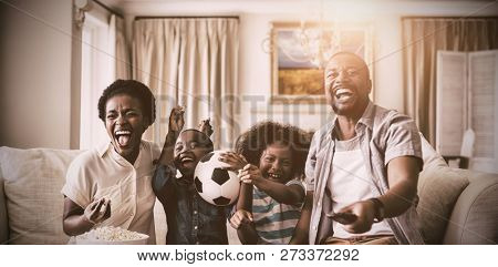Parents and kids having fun while watching television in living room at home