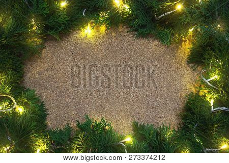 Frame Of Conifer Branches With Yellow Lights On A Wooden Board. Christmas