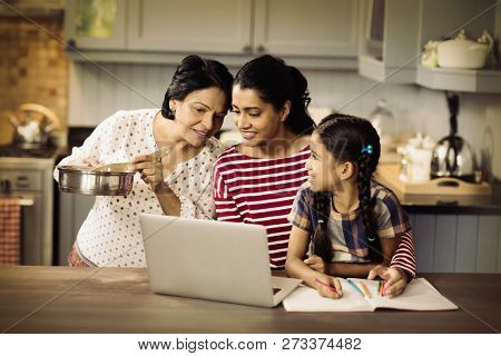 Multi-generation family using laptop in kitchen at home