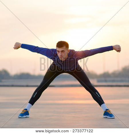 Young Male Runner Stretching Before Run at Sunset. Healthy Lifestyle and Active Sport Concept.