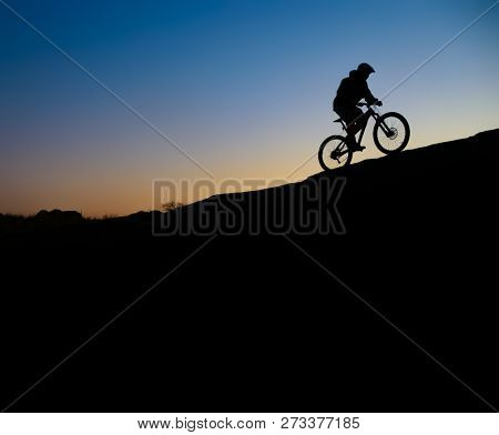 Cyclist Riding the Bike on the Rocky Trail at Sunset. Extreme Sport and Enduro Biking Concept.