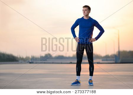 Young Male Runner Resting after Run at Sunset. Healthy Lifestyle and Active Sport Concept.