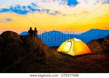 Young Couple Sitting Together on the Top of the Rock near Illuminated Hiking Tent and Enjoying the Beautiful Evening Mountain View under Sunset Sky