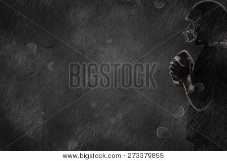 American football player in helmet standing with football against old weathered wall