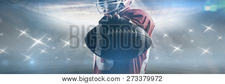 Young American football player standing in rugby helmet and holding rugby ball