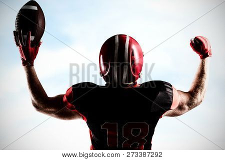 American football player standing with helmet holding football in victory against blue sky with clouds