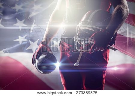 American football player holding rugby helmet and rugby ball against full frame of american flag American football player holding rugby helmet and rugby ball, Close-up