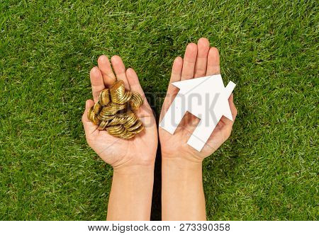 Hands Holding A House And Coins In Conceptual Image Of Mortgage Plans For Housing Investment
