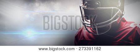 American football player standing in rugby helmet against american football arena