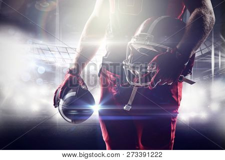 American football player holding rugby helmet and rugby ball against american football arena American football player holding rugby helmet and rugby ball, Close-up