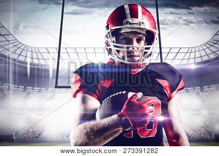 American football player in helmet holding rugby ball against football arena