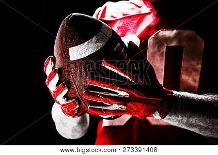 American football player holding rugby ball, Close-up