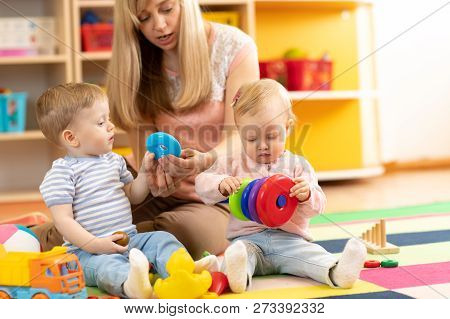 Babysitter And Children Playing Together In Nursery Or Day Care Centre