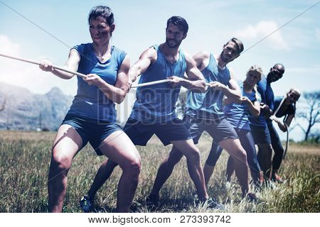 People playing tug of war during obstacle training course in boot camp