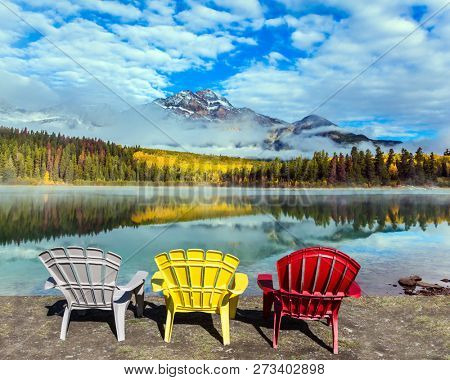 Rocky Mountains of Canada. Three comfortable multi-colored deck chairs stand by the Piramid lake.  Concept of ecological, active and photo-tourism
