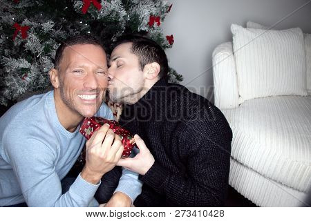 Gay Male Couple Exchanging Christmas Gift In Front Of Tree With A Kiss
