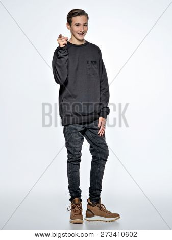 Teen boy is pointing by finger. Teenage boy dressed in black trendy clothes posing at studio. Full portrait of handsome teen boy over whitebackground.