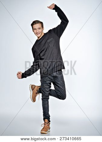 Teen boy dancing. Teenager dressed in black trendy clothes posing at studio. Full portrait of handsome teen boy over white background.