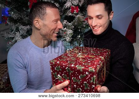 Happy Male Gay Couple Exchanging Christmas Gift In Front Of Tree With Red Ribbons