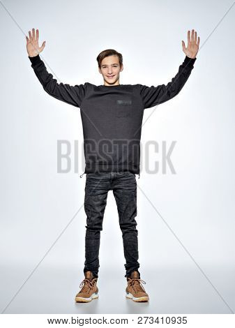 Teen boy stands at studio with raised arms. Front view. Teenage boy dressed in black trendy clothes posing at studio. Full portrait of handsome teen boy over white background.