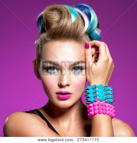 Fashion portrait of young caucasian model with bright makeup. Beautiful woman with creative hairstyle. woman with  Fashion make-up. girl with bracelets on her hands in the form of thorns. Jewelry