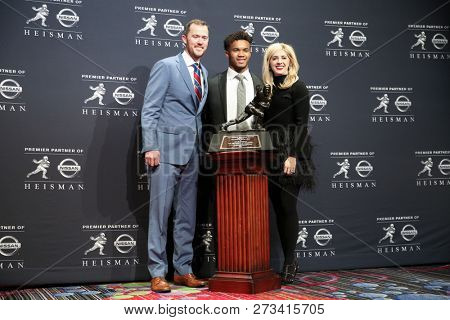 NEW YORK-DEC 8: (L-R) Oklahoma Sooners head coach, Lincoln Riley, Kyler Murray and Caitlin Buckley pose with the Heisman trophy on December 8, 2018 at the Marriott Marquis in New York City.