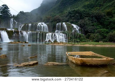 Wooden Boat In Front Of Amazing Waterfall