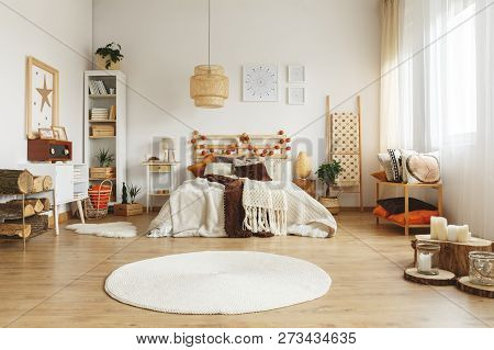 Round Rug In Front Of Bed In Spacious Boho Bedroom Interior With Rattan Lamp And Posters. Real Photo
