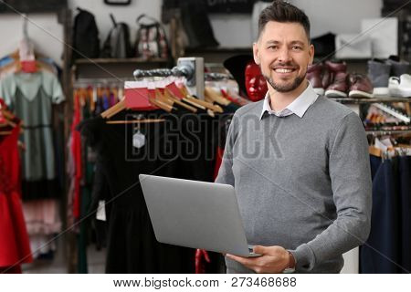 Business owner with laptop in his store